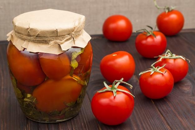 통조림 된 토마토와 신선한 토마토의 유리 항아리. 수제 발효 제품. 건강한 겨울 음식. 검은 나무 표면.