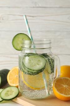 キュウリ水、スライス、木製の表面にレモンのガラスの瓶