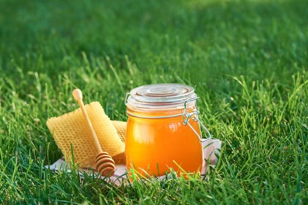 Стеклянная банка свежего меда и соты с деревянной ложкой на траве.