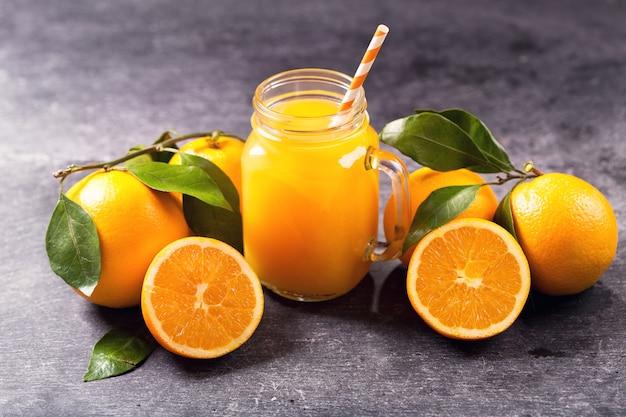 어두운 테이블에 신선한 과일과 신선한 오렌지 주스의 유리 항아리