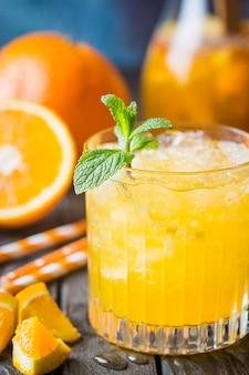 暗いテーブルに氷と新鮮な果物と新鮮なオレンジジュースのガラス瓶