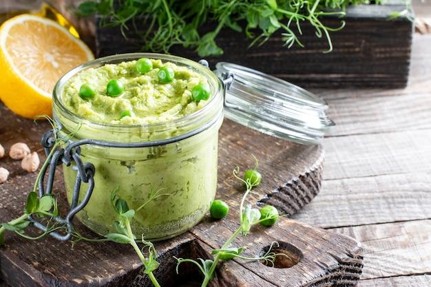 緑のフムスのガラス瓶、ひよこ豆と緑のエンドウ豆のおいしいクリーム