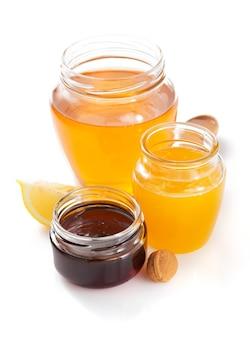 白い背景で隔離の蜂蜜のガラス瓶
