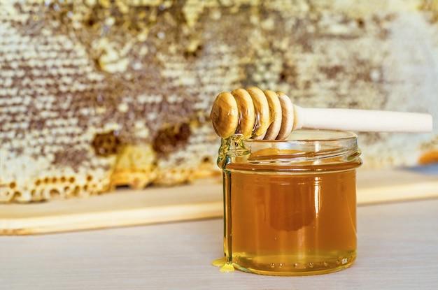 ハニカムと木製ディッパーフレームと蜂蜜のガラスの瓶。コピースペース、テキストのための場所