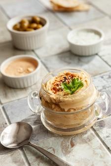 Стеклянная банка хумуса, традиционных еврейских, арабских, ближневосточных блюд из нута с глубиной и с лепешками из лаваша на фоне керамической плитки. крупным планом, выборочный фокус