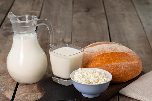 우유의 유리 항아리, 코티지 치즈와 빵 나무 테이블에 그릇을 닫습니다.