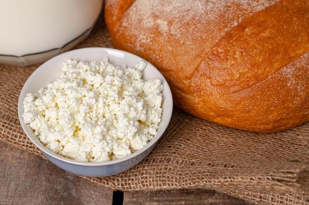 牛乳のガラス瓶、カッテージチーズのボウル、木製のテーブルの上のパンをクローズアップ