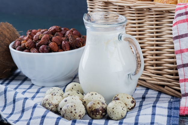 Стеклянная банка молока, сушеные финики и перепелиные яйца на скатерти.