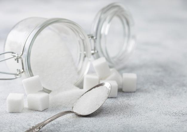 Стеклянная банка натурального белого сахара-рафинада с кубиками с серебряной ложкой на свете
