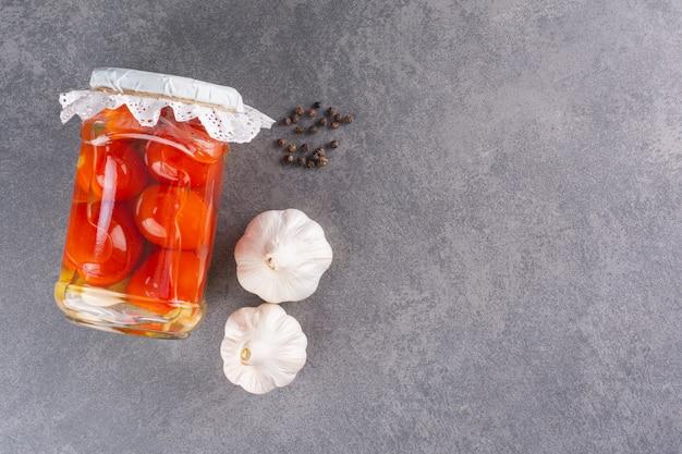 절인 된 토마토와 마늘 돌 테이블에 유리 항아리.