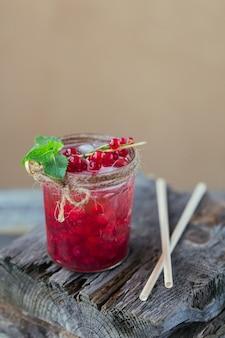 木製のテーブルに赤スグリのソーダ飲料のガラス瓶。夏の健康的なデトックスレモネード、カクテルまたは別の飲み物の背景