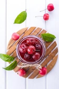 白いテーブルに新鮮な果物と小さな楽園リンゴジャムのガラスの瓶。フラット横たわっていた、トップビュー