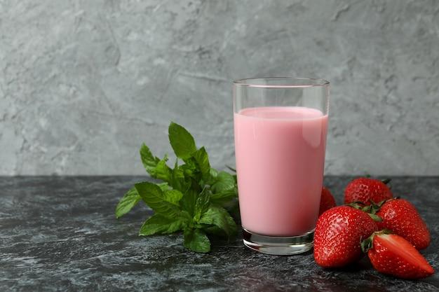 딸기 밀크 쉐이크와 블랙 스모키 테이블에 재료의 유리 항아리