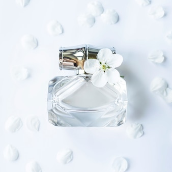 A glass jar of perfume among white spring petals