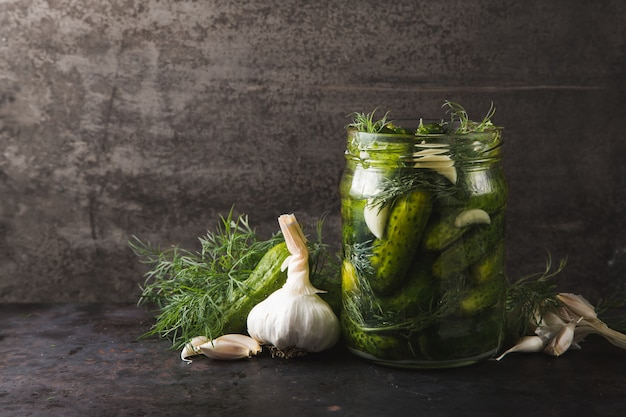 Glass jar of pickles with dill and garlic Premium Photo