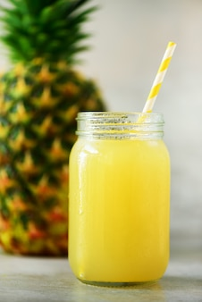 Glass jar of pineapple smoothie and whole fruit. summer, holiday concept. raw, vegan, vegetarian, clean eating diet.
