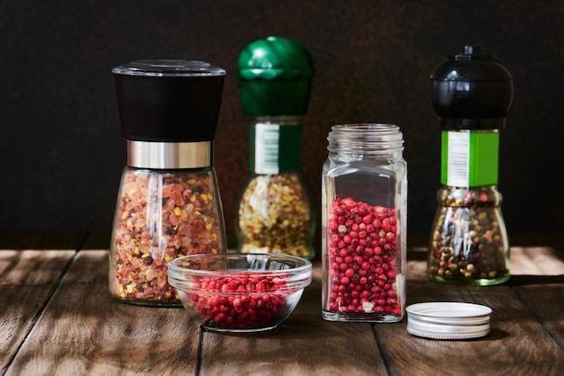 Glass jar of pink pepper and various spices in glass mills on a dark wooden table close up