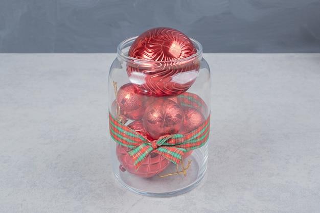 Un barattolo di vetro di palle di natale rosse su sfondo scuro. foto di alta qualità