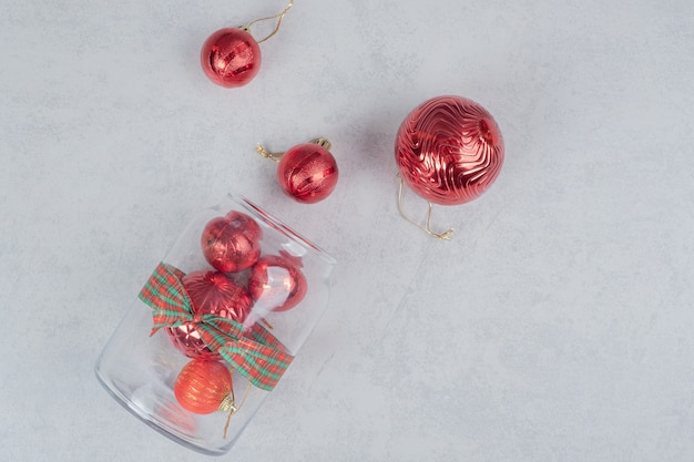 A glass jar of red christmas balls on dark background.