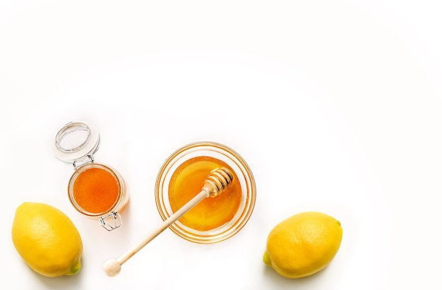 Glass jar and saucer with honey and lemons isolated on white background.