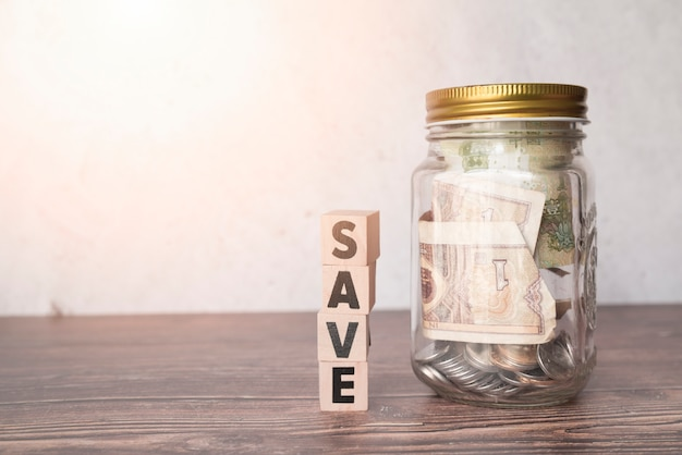 Glass jar for savings with wooden word