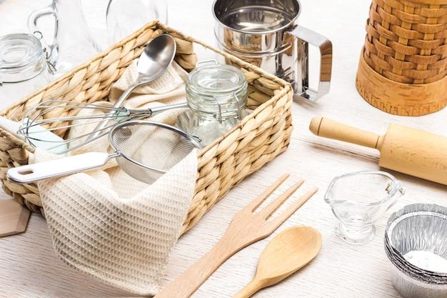 Стеклянная банка, сито и ложка в плетеной коробке. кухонная утварь для замеса теста. белый фон. вид сверху