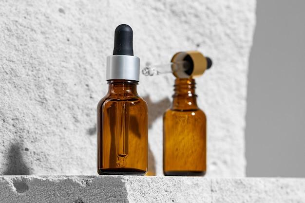 Glass jar of skincare serum on concrete block close up