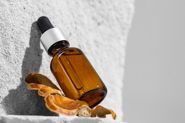 Glass jar of skincare serum on concrete block