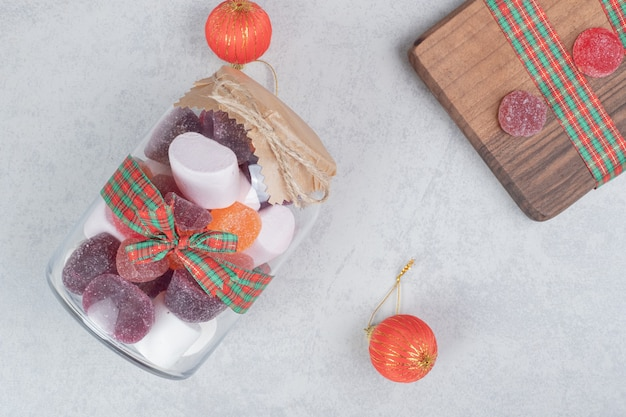 A glass jar of sweet candy on wooden board.