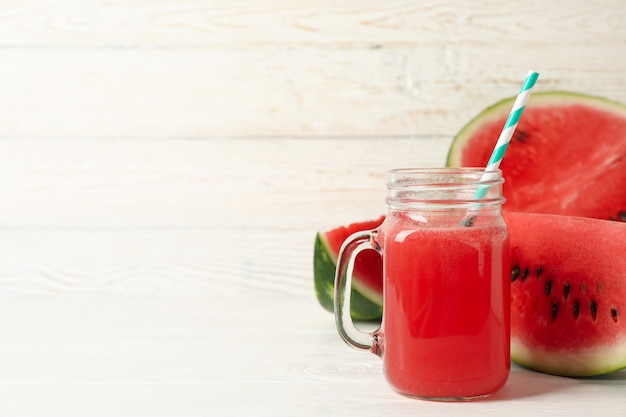 Glass jar of watermelon juice and slices on white wood
