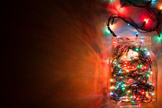 輝くガーランドの上面とガラスの瓶。テキストのためのスペース