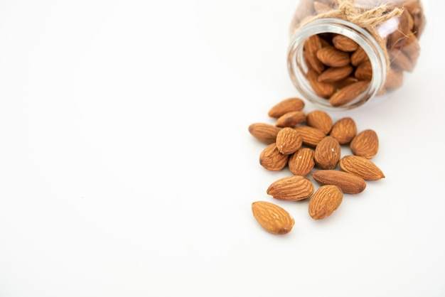 Glass jar with almond on white background.