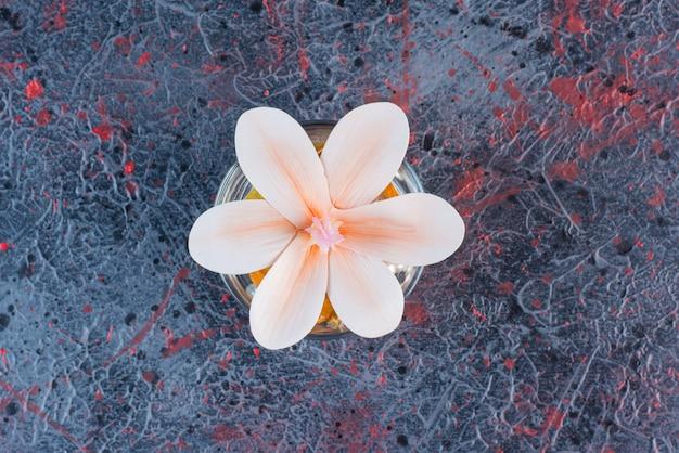 Un barattolo di vetro con un bel fiore rosa su sfondo marmo.