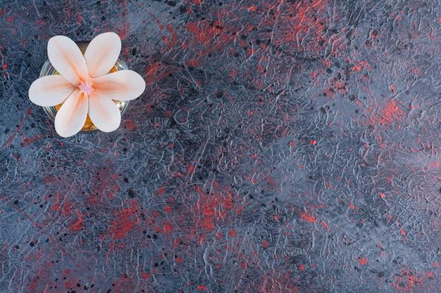 Un barattolo di vetro con un bel fiore rosa su marmo