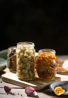 Glass jar with canned mushrooms with garlic and pepper.