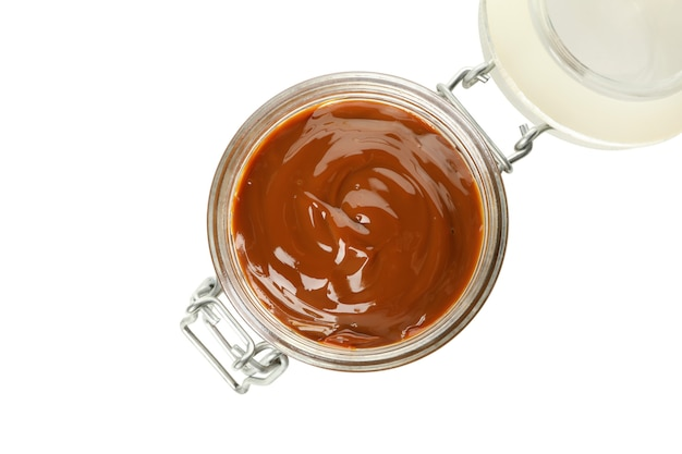 Glass jar with caramel condensed milk isolated on white background
