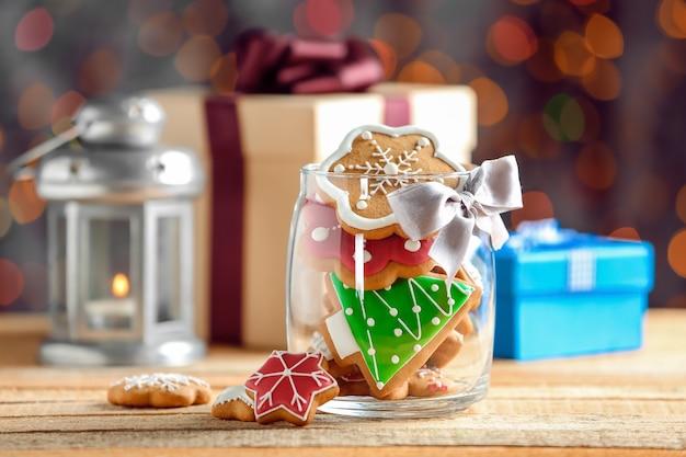 Стеклянная банка с рождественским печеньем на деревянном столе