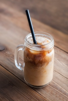 Glass jar with coffee, or latte drink with  ice cubes and  straw.