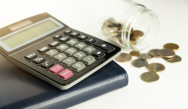 Glass jar with coins, black calculator on notepad. white background. financial concept.