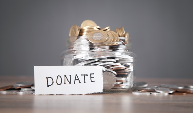 Glass jar with coins and donate word.