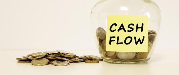 節約のためのコインが入ったガラスの瓶。メモ用紙に刻まれたキャッシュフロー。財務コンセプト。