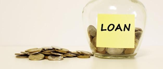 Стеклянная банка с монетами для сбережений. надпись на бланке займа. финансовая концепция.