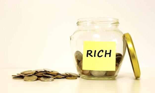 Glass jar with coins for savings. the inscription rich on the note paper. financial concept.