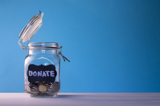 Стеклянная банка с монетами с биркой мелом пожертвуйте на синем фоне. концепция пожертвования и благотворительности. скопируйте пространство.