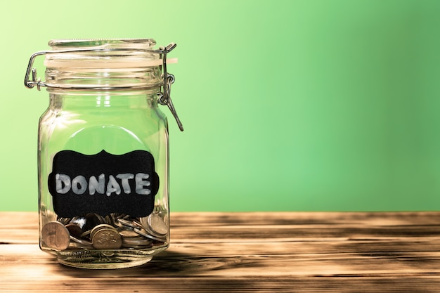 Стеклянная банка с монетами с биркой мелом пожертвуйте на зеленом фоне. концепция пожертвования и благотворительности. скопируйте пространство.