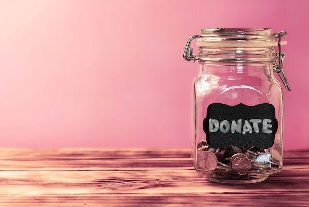 Стеклянная банка с монетами с биркой мелом пожертвуйте на розовом фоне. концепция пожертвования и благотворительности. скопируйте пространство.