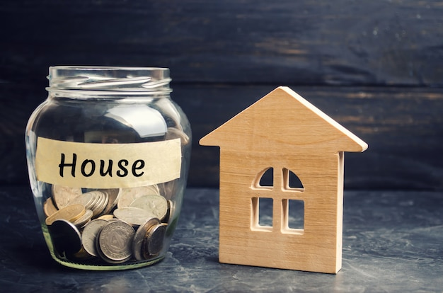 A glass jar with coins and a wooden house and the inscription house