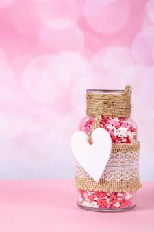 A glass jar with colorful hearts on a pink background with bokeh