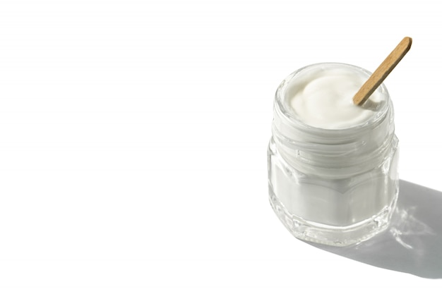 Glass jar with cream and wooden stick