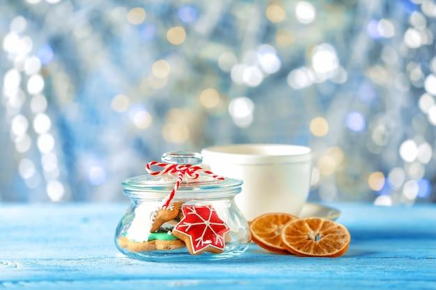 木製のテーブルに創造的なクリスマスクッキーとガラスの瓶